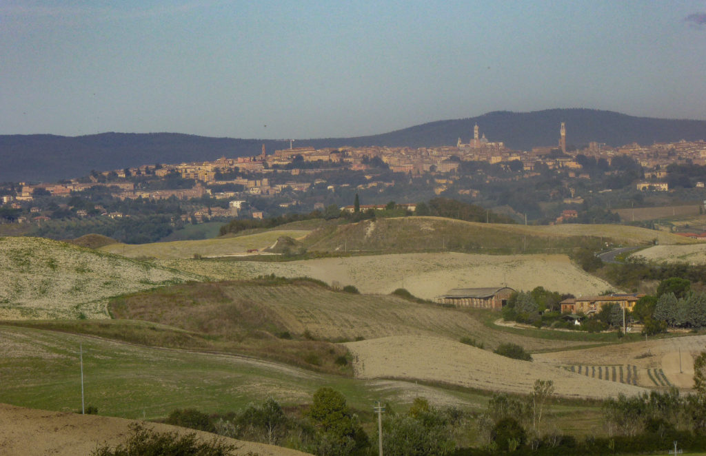 A view of Siena in the distance from Asciano in Tuscany Italy