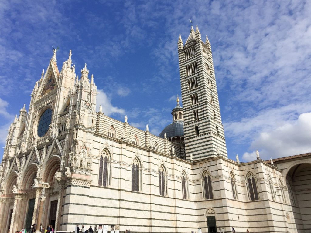 The spectacular Duomo di Siena, with its striped exterior, bluish metal dome and bell tower.