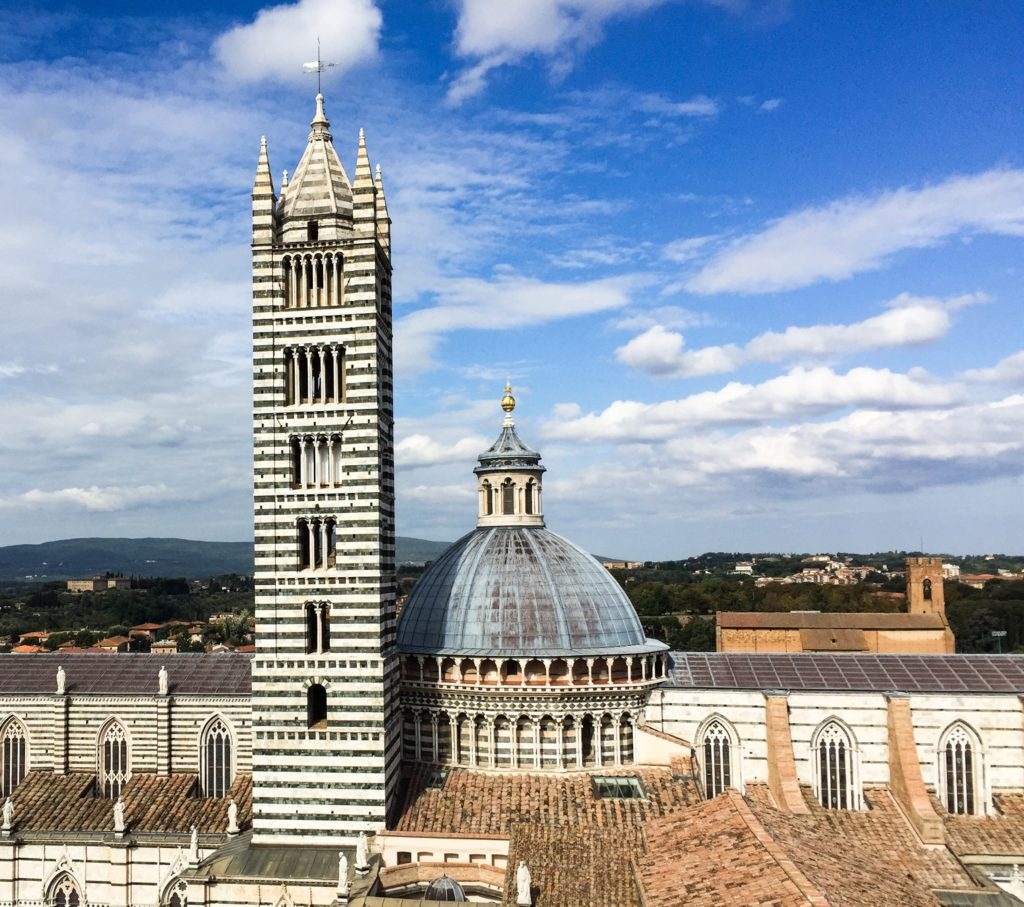 The dome and bell tower of the Duomo di Siena, seen from the Panorama dal Facciatone in Siena, Italy. The Duomo is a must-visit on your one day in Siena.