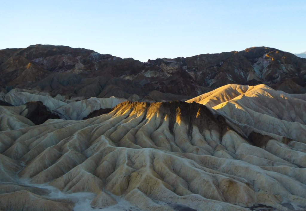 The rising sun paints the tops of the Elephant's Feet at Zabriskie Point in Death Valley National Park, California