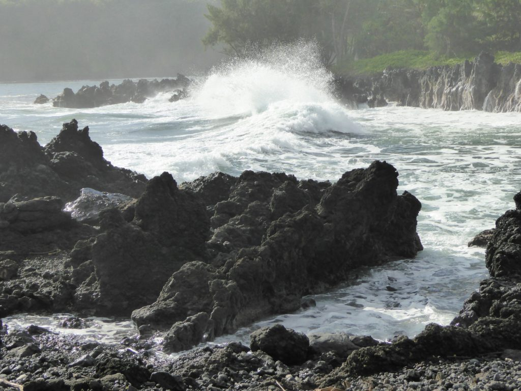 Waves crashing over rocks at Keanae Peninsula in Maui Hawaii