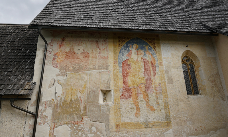 A faded mural of St. Christopher on the outside wall of the St. John the Baptist Chutch at Lake Bohinj in Slovenia